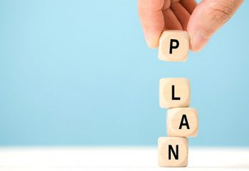 Hand hold wooden cube with PLAN word. The concept of planning in business.